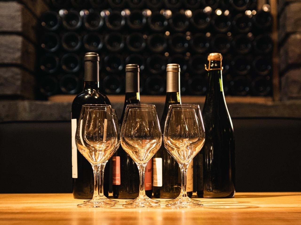 Garrafas de vinho e taças sobre a mesa e adega nos fundos